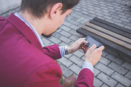 Man in Magenta Suit Jacket Holding Smartphone With Both Hands