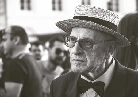 Man in Straw Hat Wearing Bow Tie With People