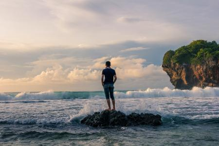 Man Standing on Stone Near Seashore during Sunrise Photography