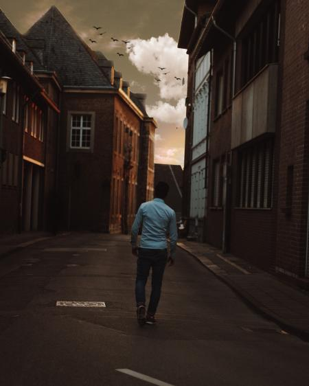 Man Walking Alone in the Street of Town