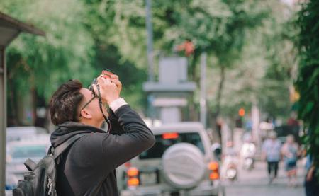 Man Wearing Black Hoodie Holding Dslr Camera Shooting on Upper Direction