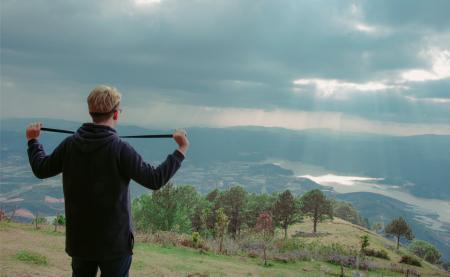 Man Wearing Hoodie Standing on Mountain Under Cloudy Sky