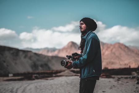 Man Wearing Jacket Holding Dslr Camera on Desert