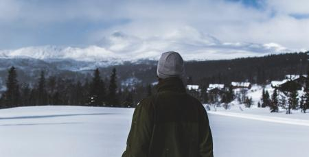 Man With Black Jacket and Grey Knit Cap Standing on White Snow Field