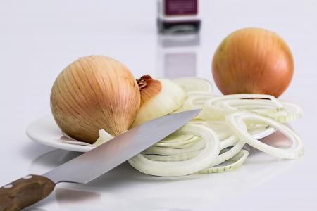 Onion Bulbs and Sliced Onion on Ceramic Plate