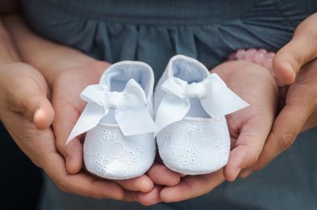Person Carrying Pair of Baby's White Flats