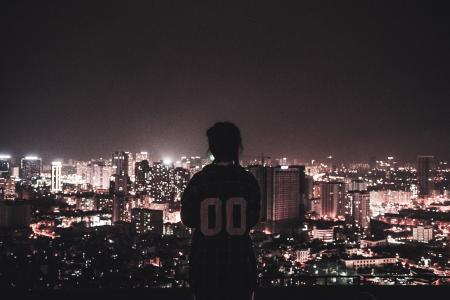 Photo of a Person Watching over City Lights during Night Time