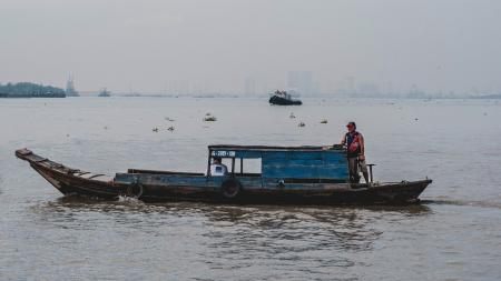 Photo of Man on Wooden Boat