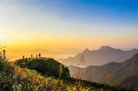 Photo of People Standing on Top of Mountain Near Grasses Facing Mountains during Golden Hours