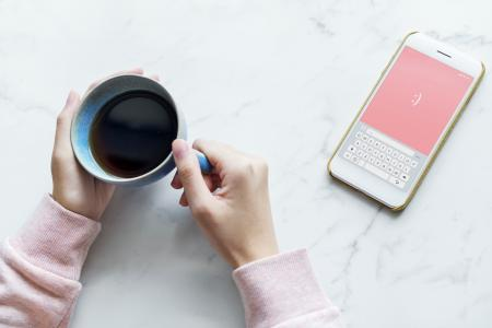 Photo of Person Holding Blue Cup Near Smartphone