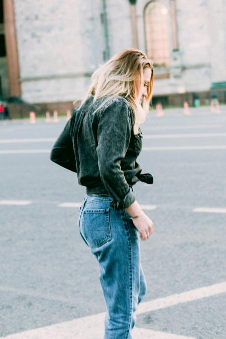 Photo of Woman Wearing Black Denim Jacket and Blue Jeans