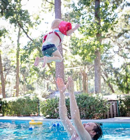 Photography of Man on Swimming Pool Tossing Toddler Above Pool