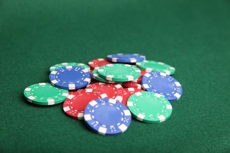 Pile of poker chips on green felt.