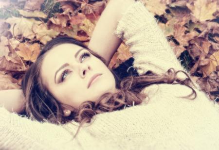 Portrait of Dreamy Woman on Autumn Leaves
