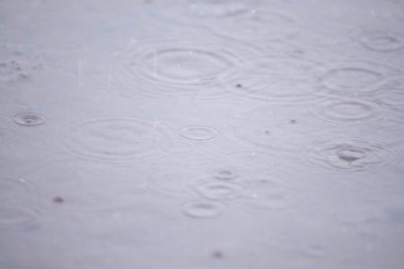 Rain drops on small water puddle