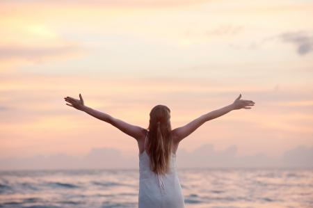 Rear View of Woman With Arms Raised at Beach during Sunset