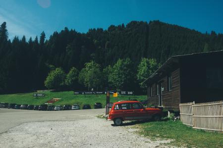 Red 5-door Hatchback Near the Brown Wooden House in Daytime