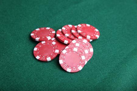 Red poker chips on green felt.
