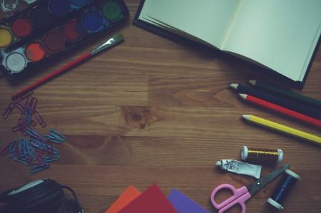 Red Yellow Blue Color Pencil Beside White Printer Paper on Brown Wood