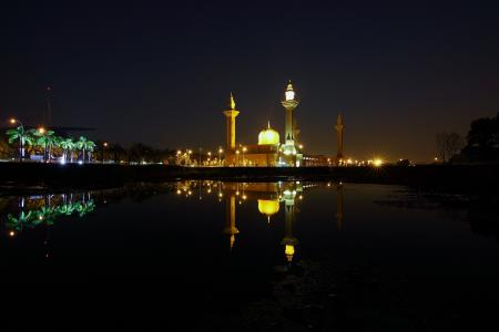 Reflection of Yellow High Rise Tower during Night Time