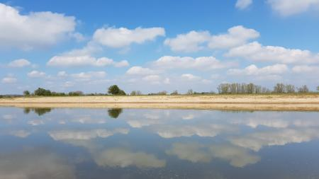 Reflection-of-blue-sky-and-white-clouds-in-water-like mirror