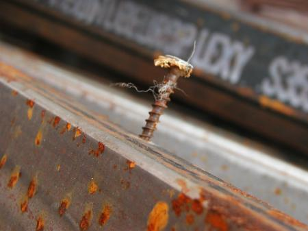 Rusted screw in metal bar
