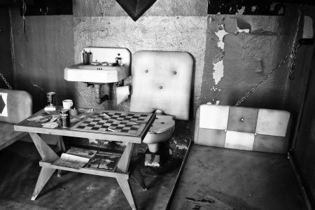 Scary old prison cell with a toilet and a chessboard