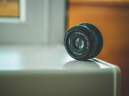 Selective Focus Photography of Black Telephoto Lens on White Table