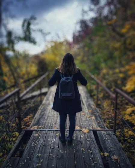 Selective Focus Photography of Woman Wearing Black Overcoat Standing on Wooden Bridge