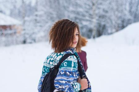 Selective Focus Portrait Photograph of Woman Wearing Blue, Green, and White Tribal Jacket and Black Backpack Outfit