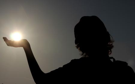 Silhouette of a child holding the sun
