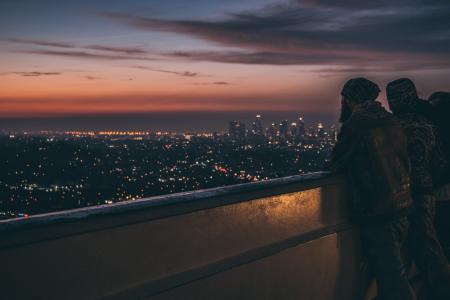 Silhouette of People Leaning on Metal Railings