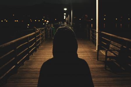 Silhouette of Person in Hoodie on Boardwalk at Night