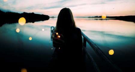 Silhouette of Woman Leaning on Metal Railings With Background of Body of Water by the Shoreline