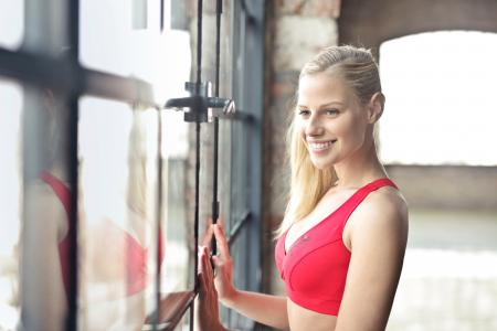 Smiling Woman In Red Brassiere Near Glass Window
