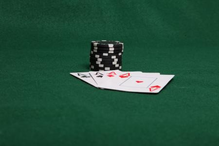 Stack of black poker chips with four ace