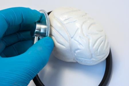 The doctor examines the human brain with a stethoscope