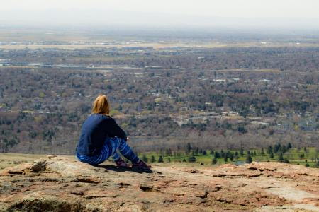Thoughtful girl in a blue jumper on the edge of the mountain