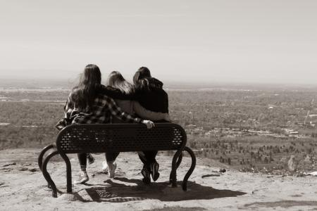 Three girls having fun on the bench in the mountains