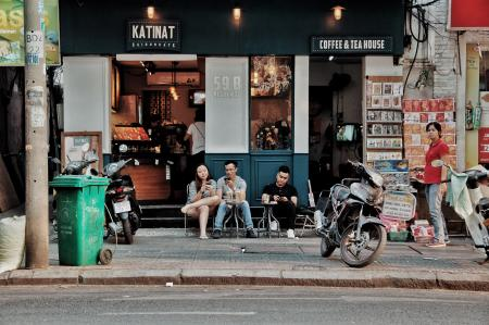 Three People Sitting on Chairs Outside Coffee & Tea House Near Motorcycles