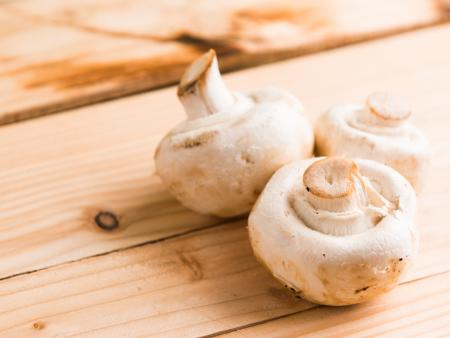 Three White Mushrooms on Beige Wooden Table