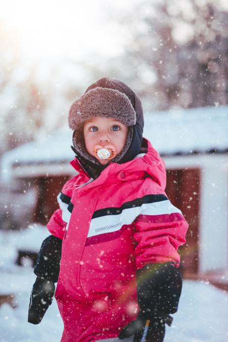 Toddler Boy Wearing Red and Black Winter Jacket and Gray Ushanka Hat Standing on Snow Covered Field