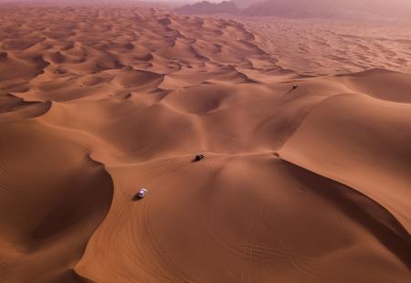 Two Vehicles on Desert Dunes