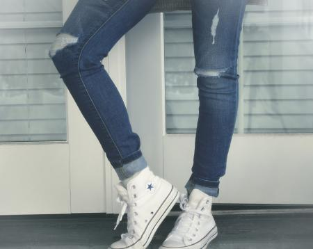 Urban Girl - Close-Up of Legs - Ripped Jeans and Sneakers
