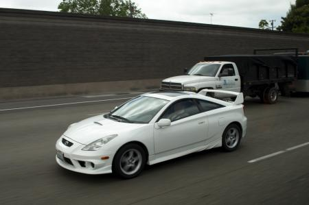 White sports car and truck on highway