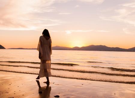 Woman iIn White Dress Walking On Beach