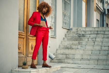 Woman in Black and Blue Sports Bra and Red Pants Standing in Front of Brown Wooden Doors Near Gray Concrete Stairs