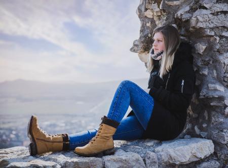Woman in Black Coat Sitting on Rock