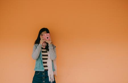 Woman in Blue Jacket Holding Pink Fujifilm Instax Camera
