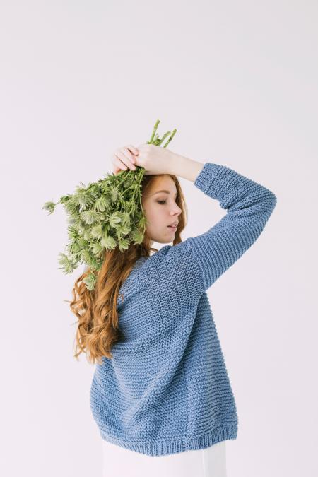 Woman in Blue Knit Cable Sweater Holding Green Petaled Flowers